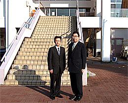 県立あすなろの郷の管理棟前で井手よしひろ県議(右)と高崎進県議