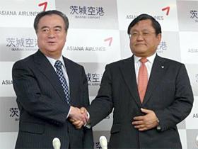 会見後に握手をする橋本知事(左)とアシアナ航空ヒョン・ドンシル日本地域本部長